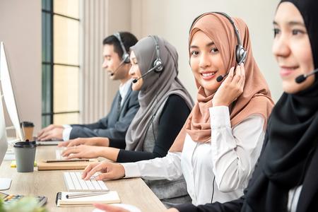 Belle femme musulmane asiatique sympathique portant un casque de microphone travaillant comme opérateur de support client avec une équipe dans le bureau du centre d'appels