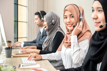 Friendly beautiful Asian muslim woman wearing microphone headset working as customer support operator with team in call center office Stock Photo