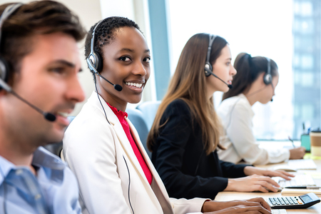 Smiling beautiful African American woman working in call center office with diverse team as the customer care operators 免版税图像