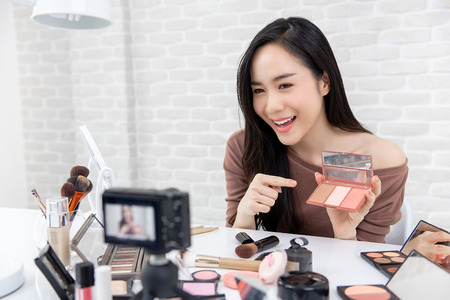 Young pretty Asian make up artist beauty blogger recording a video show tutorial about cosmetics Banco de Imagens