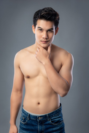 Portrait of shirtless young handsome Asian man wearing jeans studio shot isolated on gray background