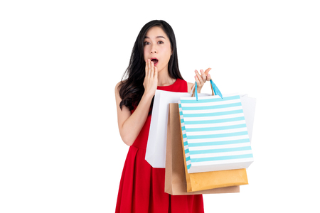Studio portrait of amused pretty Asian woman shopper holding shopping bags in a shocking gesture