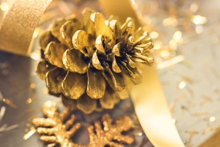 Golden colored pine cone with shiny curly ribbon for Christmas  decoration