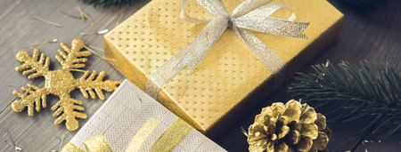 Sliver and gold shimmer Christmas gift boxes and decoration items on wood table, banner festive background