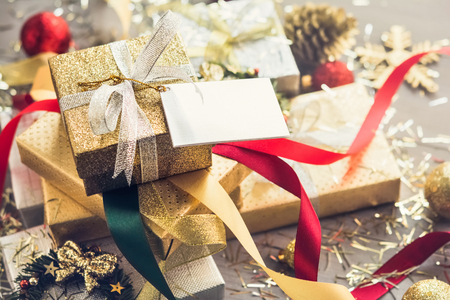 Pile of glittering silver and gold Christmas gift boxes with colorful curly ribbons and decorating items on the table