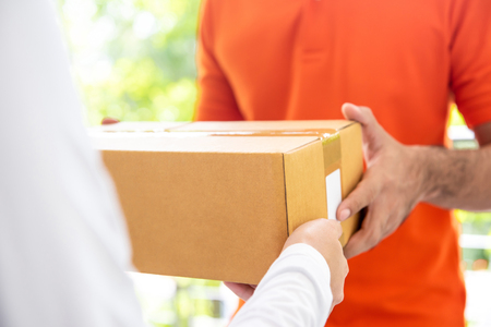 Courier service delivery man in orange uniform giving parcel box to customer at home Imagens