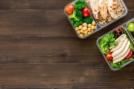 Schoon, gezond, vetarm, kant-en-klaar voedsel in afhaalmaaltijdensets op houten tafelachtergrond bovenaanzicht met kopieerruimte
