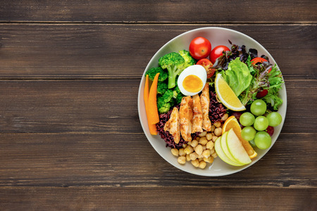 Clean healthy low fat ready to eat food with mixed vegetable and fruit salad in round shape dish on wood table background top view with copy space Imagens