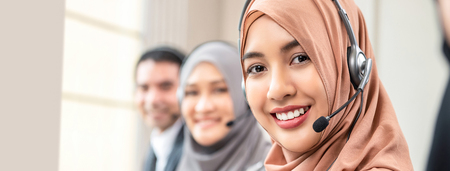 Friendly beautiful Asian muslim woman wearing microphone headset working as customer service operator with team in call center office, panoramic web banner Imagens