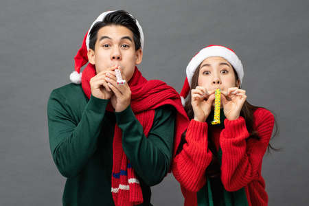 Playful Asian couple in colorful red and green Christmas sweaters with hats blowing party horns for fun studio shot gray background