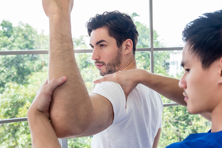 Physical therapist giving masssage and stretching athlete male patient shoulder and arm in clinic
