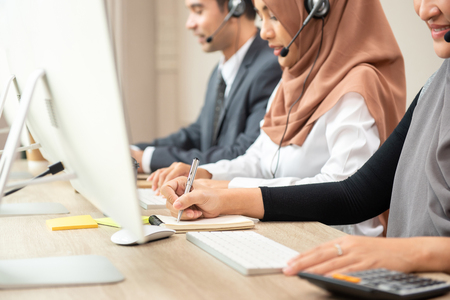 Muslim customer service team wearing microphone headset working in call center office