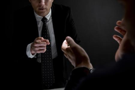 Detective pointing hand to suspect or criminal man in dark interrogation room