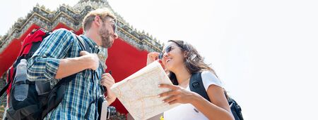 Young tourist couple backpackers traveling in ancient Thai temple on summer vacations in Bangkok Thailand, panoramic banner with copy space