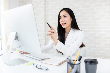 Smart beautiful Asian businesswoman working on computer searching for information online in the office