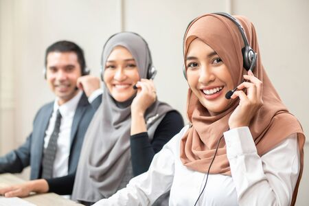 Smiling Asian muslim women wearing microphone headsets working as customer care operators with team in call center office