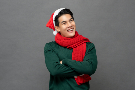 Smiling happy Asian man wearing colorful red and green Christmas theme clothes with arms crossed looking at copy space aside isolated on gray background