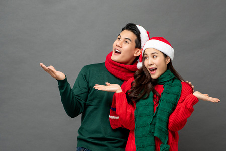 Excited happy young Asian couple wearing Christmas theme clothes with open palms gesture studio shot isolated on gray background