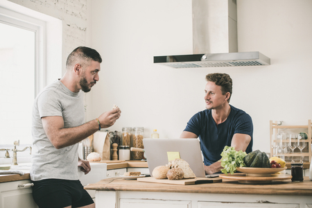 Gay male couple seriously talking at home while doing morning routines, LGBT lifestyle concept Imagens