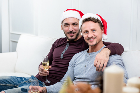 Happy gay male couple celebrating Chritsmas at home sitting on the couch drinking champagne Imagens