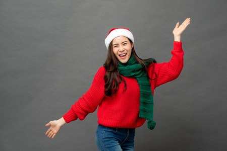 Happy playful Asian woman in red and green Christmas attire studio shot on gray background