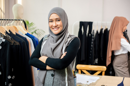 Asian muslim woman designer as a startup business owner in her tailor shop