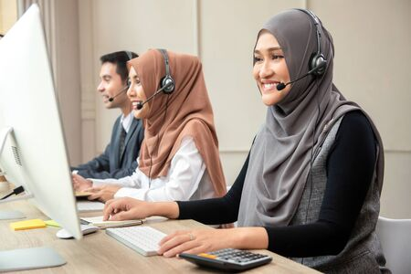 Smiling Asian muslim woman wearing microphone headsets working as customer care operator with team in call center office