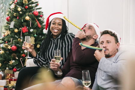 African american woman with group of friends celebrating Christmas at home drinking champagne
