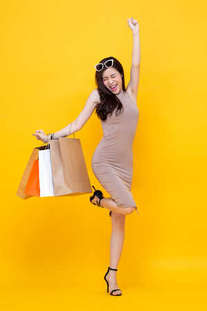 Happy excited Asian woman with shopping bags for sale concept, studio shot isolated on colorful yellow background Imagens