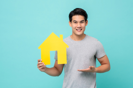 Portrait of young handsome Asian man holding paper home for real estate concept