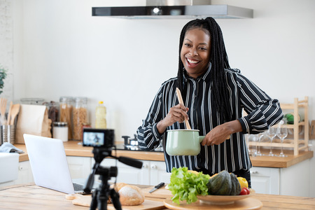 Happy african american woman vlogger broadcasting live video online while cooking food in kitchen at home