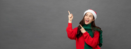 Happy beautiful Asian girl wearing Christmas attire pointing hands to empty space aside studio shot on gray banner background Imagens