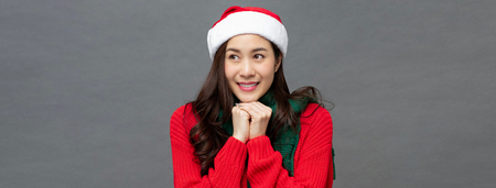 Studio portrait of excited asian woman wearing christmas themed attire in an anticipating gesture on gray banner background