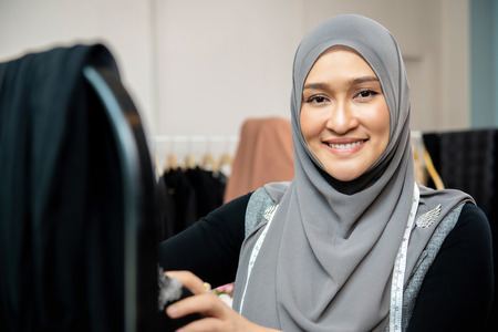 Asian muslim woman designer as a startup business owner working in her tailor shop Imagens