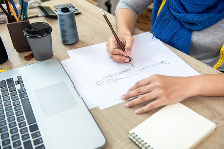 Muslim woman fashion designer drawing a dress design sketch in paper at the table