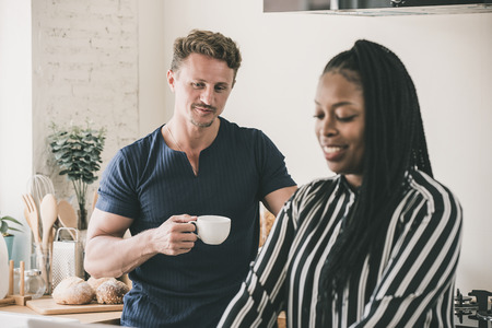 Married life morning routine of interracial couple in the kitchen at home