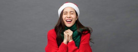 Young pretty Asian woman wearing red Christmas sweater and hat in surprised excited emotion on gray banner backround Imagens