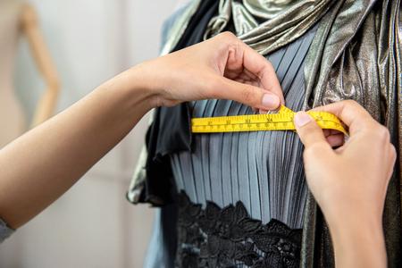 Muslim designer measuring size of dress with measurement tape in tailor shop Imagens
