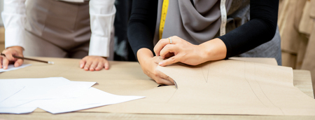 Muslim woman dressmaker cutting clothing pattern at the table in tailor shop, panoramic banner