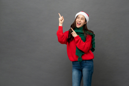 Happy beautiful Asian girl wearing Christmas attire pointing hands to empty space aside