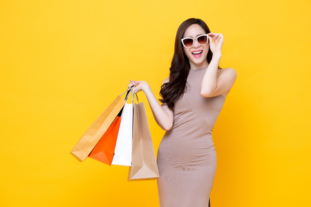 Happy beautiful Asian shopaholic woman carrying shopping bags in colorful yellow background, summer sale concept Imagens