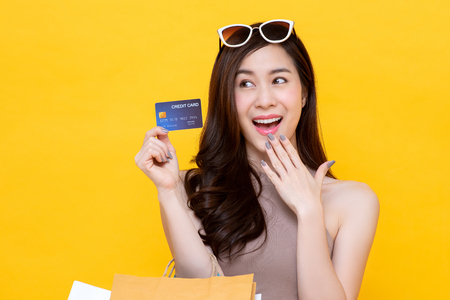Beautiful smiling Asian woman carrying shopping bags showing credit card in hand studio shot isolated on colorful yellow background Imagens