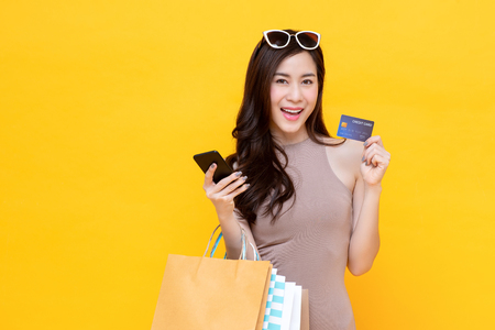 Beautiful smiling Asian woman with shopping bags showing credit card in hand studio shot isolated on colorful yellow background
