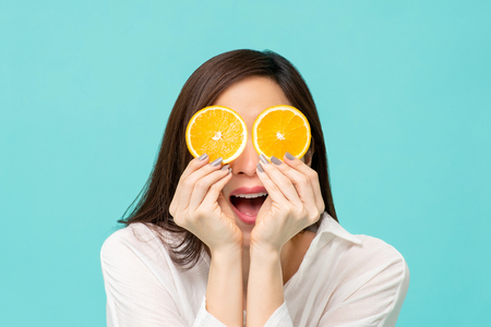 Young woman with fresh sliced oranges at the eyes studio shot isolated on light blue background