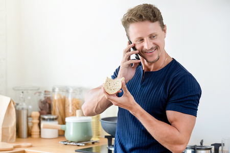 Casual man eating bread as breakfast and talking on cell phone in the morning at home Imagens