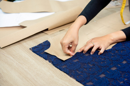 Designer hands pinning paper pattern on fabric at the table making dress in tailor shop Imagens