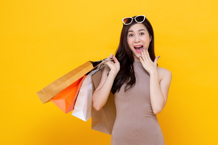 Young Asian woman carrying colorful shopping bags in surprised and excited gesture studio shot isolated on yellow background