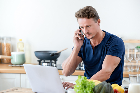 Casual man calling on cell phone while working on laptop computer at home in the morning
