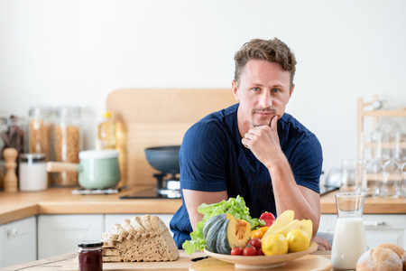 Healthy man in the kitcken with wholesome food for breakfast on the table