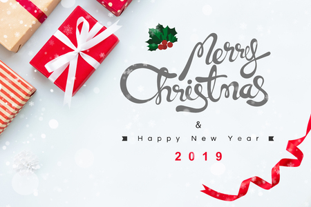 Merry Christmas and Happy New Year 2019 greeting text with gift boxes white snow and curled red ribbon at border, top view Imagens